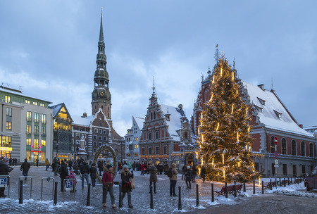 RIGA, LATVIA - JANUARY 03, 2017: Christmas tree, decorated with toys and candles, against the background of the blackheads house in Riga and the Tower of St. Peters Church