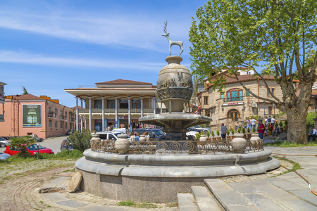 Sighnaghi, Georgia - May 06, 2019: One of the central squares of the city, located near the wedding palace, with a fountain in the center in the form of a jug with a deer standing on top