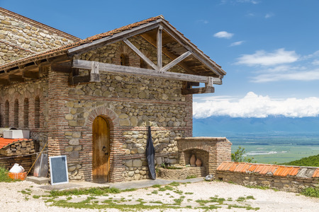 Sighnaghi, Georgia - Fragment of an old stone building on the territory of the Bodbe Monastery on the background of the Alozansk Valley in the Kakheti region and a blue sky