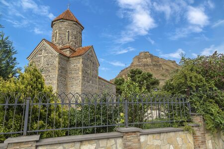 Gori, Georgia - Temple of the Holy Archangels against the backdrop of a medieval fortress in the city of Gori