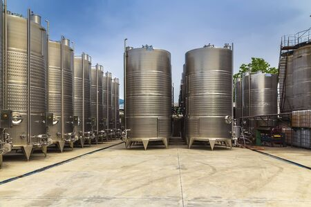 Large metal containers for fermenting and making wine outdoors under a blue sky on a clear cloudless day Stock fotó