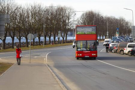 Riga, Latvia - March 28, 2019: A red sightseeing bus travels through the streets and embankments of the Daugava in Riga at a sunny sunset time