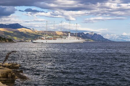 Ship with five masts on a background of mountains and cloudy sky Stock fotó