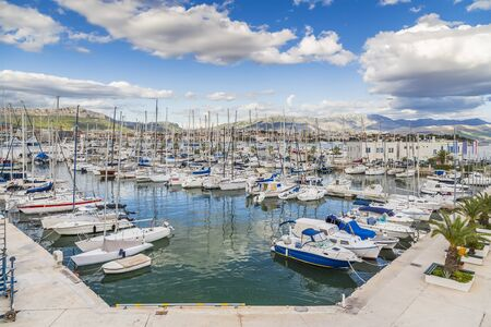 Split, Croatia - Marina with many yachts on the background of picturesque mountains on the horizon and cloudy sky