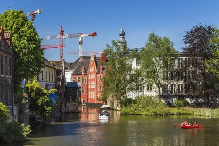 Ghent, Belgium-may 07, 2018: Sightseeing trips on the Lys river and city canals by motor boats and paddle kayaks