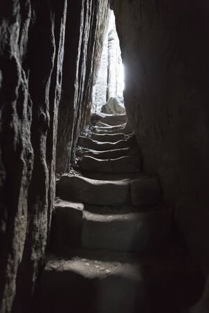 A narrow stepped passageway between two overhanging rocks and a view of light at the end of this tunnel