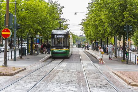 Helsinki, Finland-August 05, 2019: One of the Central streets of the city, tram traffic, pedestrian crossing and people waiting for city transport at the tram stop. Standard-Bild
