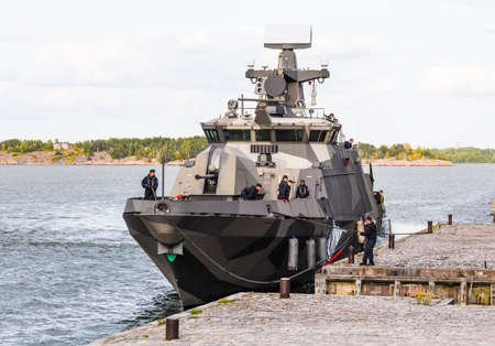 Helsinki, Finland - August 05, 2019: NATO warship with people on its deck docks at the pier in Suomenlinna on a Sunny summer day.