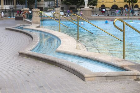 Szechenyi Baths - a small ditch for rinsing the feet before entering a large swimming pool with blue water and bronze handrails