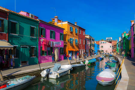 Burano, Italy-November 01, 2014: Canal, houses, passers-by tourists, motor boats and Laundry drying on ropes