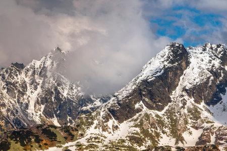 Poland, Zakopane - High Tatras, a light smoky cloud entangled between two mountain peaks of the mountain range on the very border between Poland and Slovakia