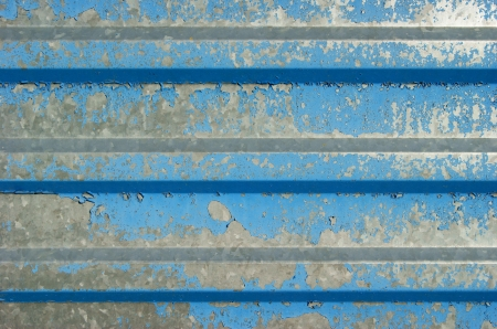The goffered metal fence with the remains of blue paint   photo