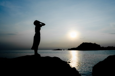 sadness: woman cry stand inside the sea sunset alone Stock Photo