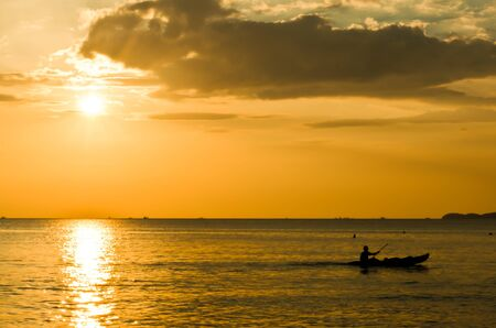 Fishermen in boat at sunset Stock Photo
