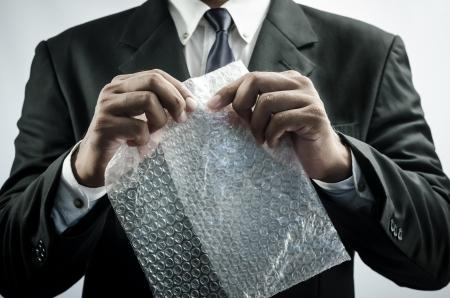 ビジネス男面白いプラスチック バブルラップでリラックスします。