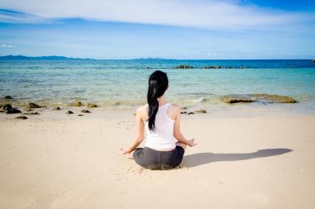 young beautiful woman meditation on beach Stock Photo