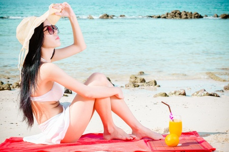 Asian woman on beach drinking cocktaill