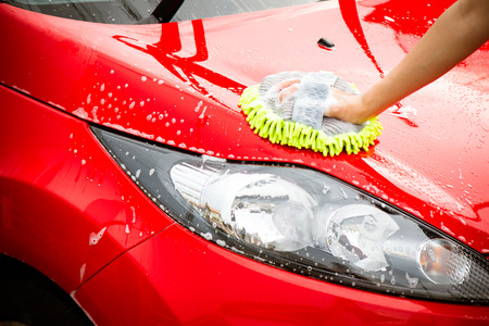 clean car: Close-up Of Hand With green Brush Washing Red Car Stock Photo