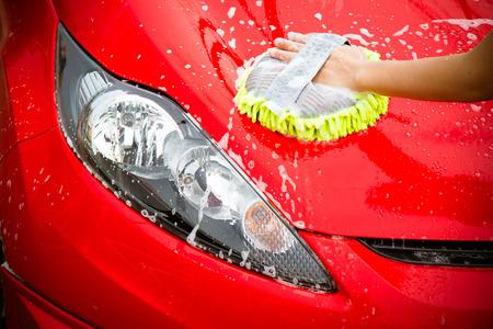 クローズ アップの手で緑のブラシ洗浄赤い車