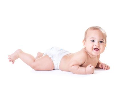 bebes niñas: Bebé sonriente feliz linda que pone el uso de pañal, aislado. Foto de archivo