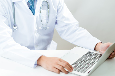 Doctor at work, close up of male doctor typing on a laptop
