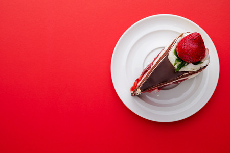 top view of Chocolate cake with strawberries on a red background