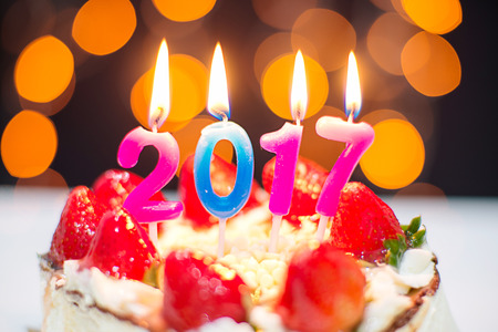 sweet seventeen: New Year 2017 still life. close up strawberry cake  with burning candles on bokeh background Stock Photo