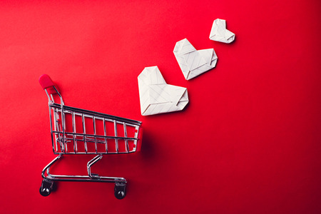 cart: shopping cart and paper heart on red background Stock Photo