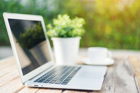 ノート パソコンと木製のテーブルの上のコーヒー 写真素材
