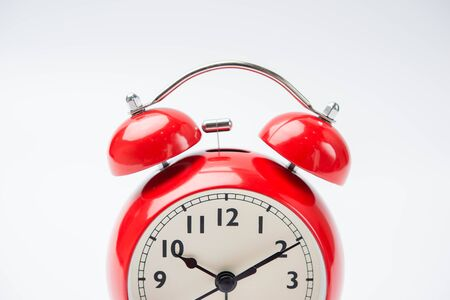 working hours: close up of a vintage red bell clock on white background