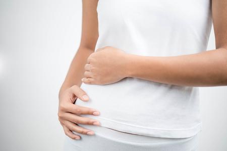 若い女性は彼女の右側の痛みに触れます。腎臓の炎症と治療。医学と医療の概念。白背景