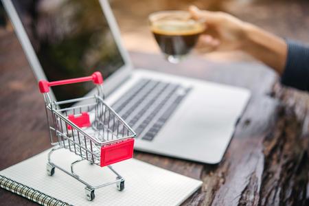 Carro de compras rojo y portátil en la mesa de madera, concepto de compras en línea.