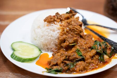 Fried lamb with curry paste on the cooked rice