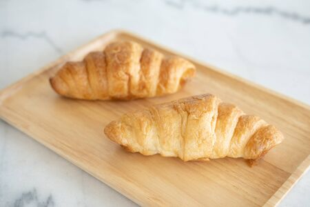A Couple of Croissants on the wooden plate