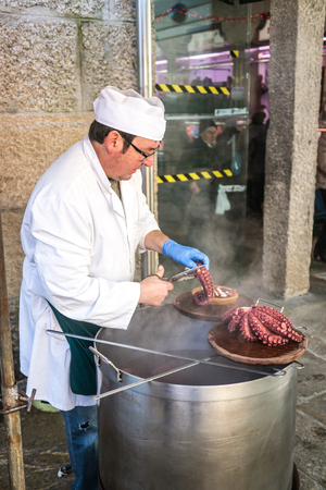 Santiago de Compostela, Spain - December 14, 2013 - Man selling tables of just cooked octopus galician style in the Abastos Market in Santiago de Compostela