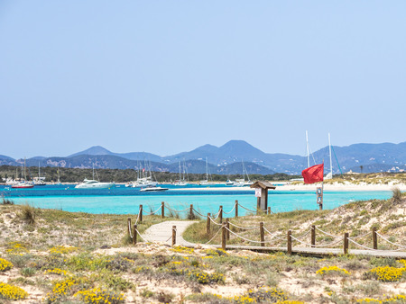 Red flag on Ses illetes beach, Formentera (text translation: Do not cross; images under red flag indicates not to cross swimming or by boat ) Banco de Imagens - 108518885