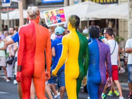 BARCELONA, SPAIN - JUNE 27, 2015: Three men creating the gay flag with their painted bodies during Gay pride parade in Barcelona, Catalonia, Spain Publikacyjne