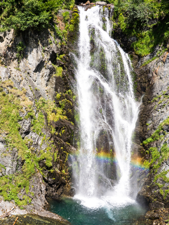 View of the rainbox colors in the Sauth des Pish waterfall in Aran valley, Spain