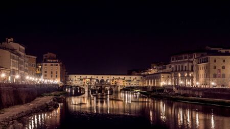 Firenze, Italy - May 27, 2017 - Reflections of the Ponte Vecchio (Vecchio Bridge) on the Arno river at night