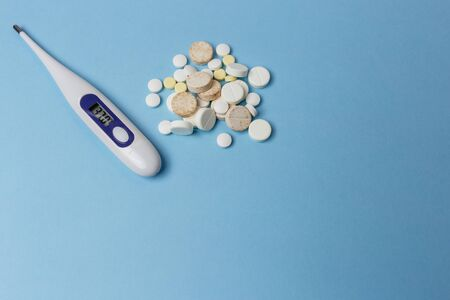Close up of a thermometer and pills various kinds lay on a light blue background