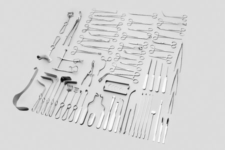 Big set of medical instruments used for surgical operations, for abdominal surgery. Made of stainless steel, sorted by tool type, laid out on a gray background