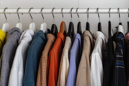 Close-up view of clothes hung on hangers in the dressing room on the white bar