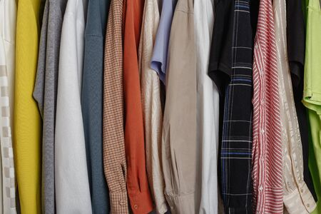 Close-up view of clothes hung on hangers, variety of clourful sleeves in photo