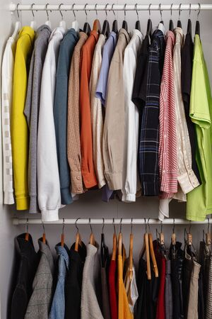 Front view of clothes hung on hangers in the dressing room on the white bar
