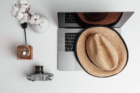 A top view of white vase of cotton flowers on a table, old-fashioned camera, time-worn lamp and vintage straw hat lying on a notebook. Soft and calm concept of old time things with modern electronics