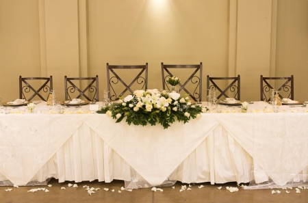 table and chairs: Main table at a wedding reception with beautiful flowers