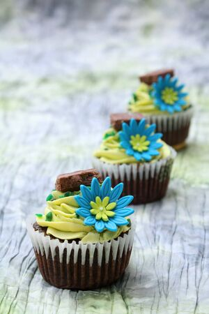 Three chocolate cupcakes decorated with icing and flowers photo