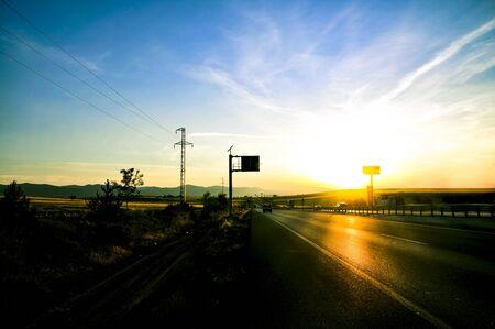 Asphalt road and mountains with foggy nature landscape at sunset. Banco de Imagens