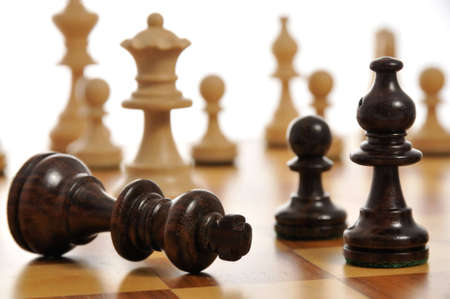 concede: The black king surrendering on a chess board Stock Photo