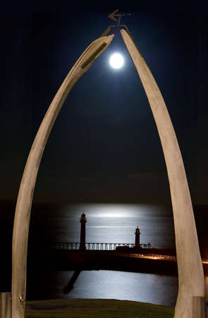 Whitby moonrise over piers seen through whale-bone archway.